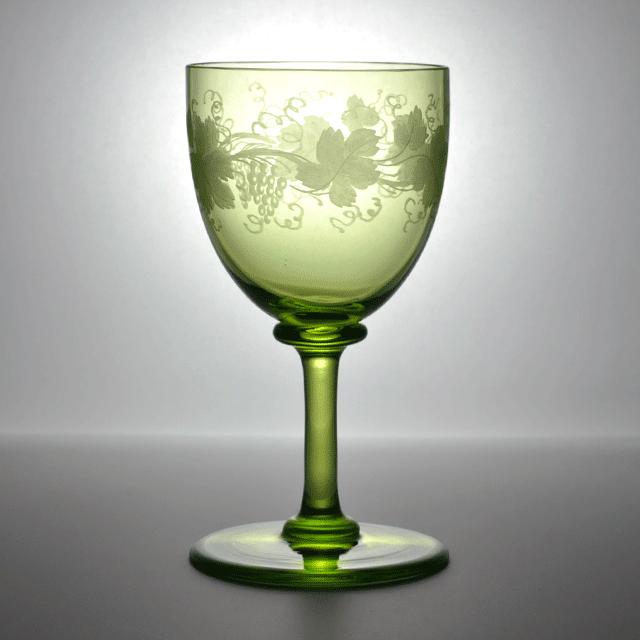 微量のウランを混ぜて作られたグリーンの色合いに繊細なエングレービングの技法でグレープやリーフが描かれたアンティークワイングラス
